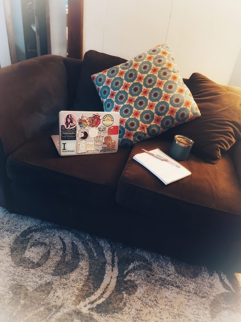 A brown microfiber sofa with a notebook, laptop covered in stickers and mug of coffee on the cushions