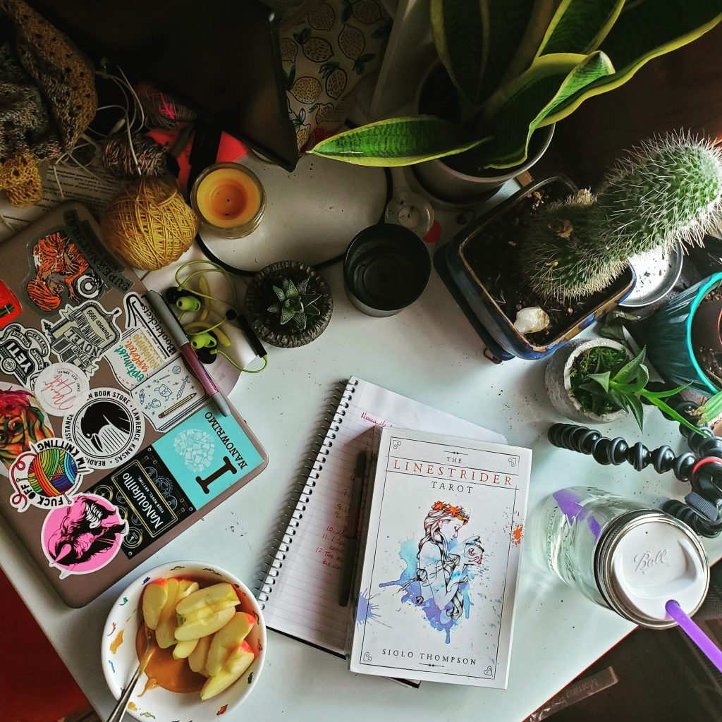 A messy white desk filled with plants and notebooks and a laptop covered in stickers